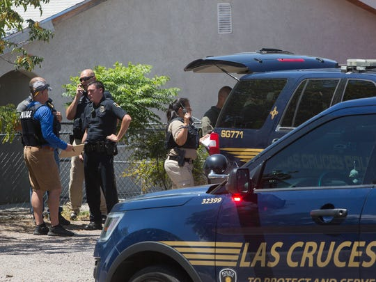 Las Cruces Police officers gather near the end of Arizona Avenue, where they set up a staging area before a SWAT team moves into location before noon on Monday July 17, 2017. Later in the day, LCPD announced a 52-year-old man had been shot dead during the incident.