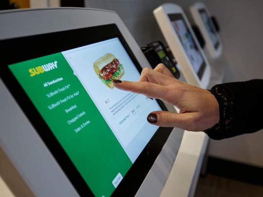 This January 2017 photo provided by Subway shows the use of new ordering tablets at a remodeled Subway store in Knoxville, Tenn. Subway is looking to update the look of its stores as the chain's U.S. sales have been declining. The company says the redesign, which includes a brighter atmosphere, displays of vegetables behind the counter and ordering tablets, is the first major revamp since the early 2000s. (Chris Radcliffe/Subway via AP)