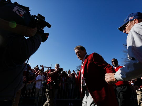 Alabama coach Nick Saban is grabbed by a fan during the NCAA college football championship parade, Saturday, Jan. 20, 2018, in Tuscaloosa, Ala. Alabama won the national championship game against Georgia 26-23 in overtime. (AP Photo/Brynn Anderson)
