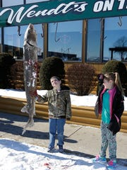 James and Hailey Binning of Blackwolf look at a sturgeon caught by Thomas Goodard of Oshkosh Saturday morning at Wendt's on the Lake, along the southwest shore of Lake Winnebago. The sturgeon was 80 pounds and 71 inches long.