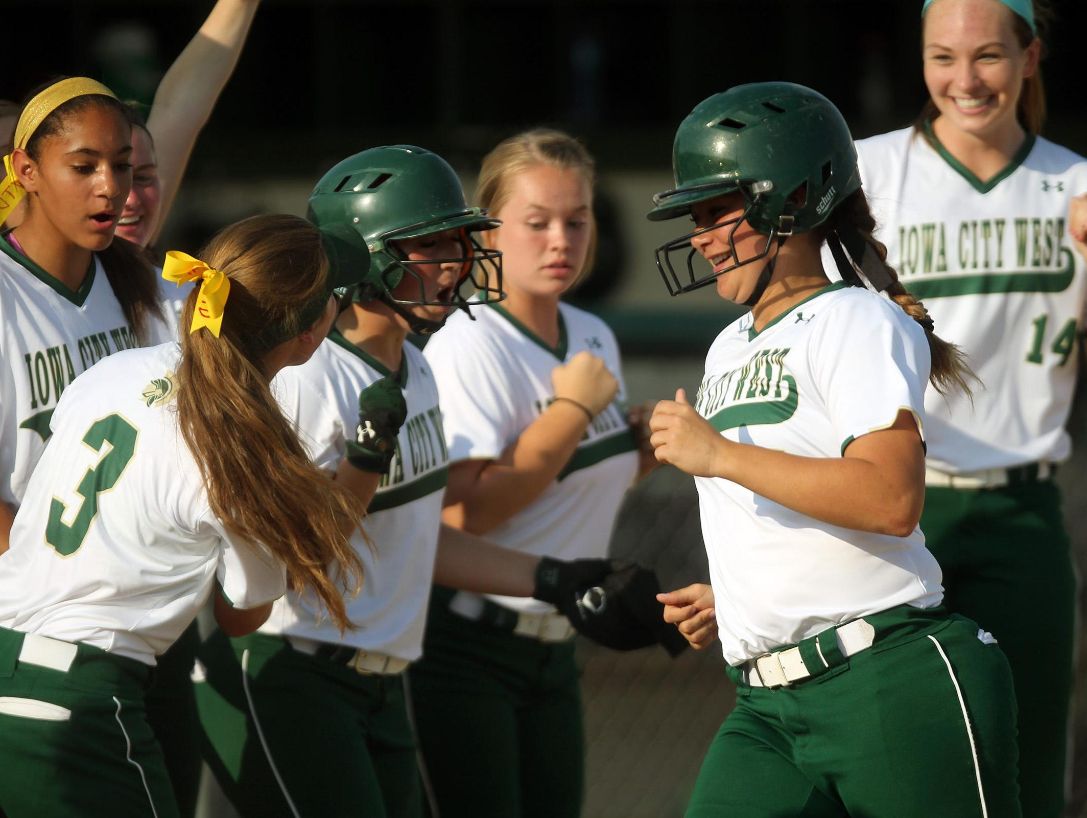 West High's Taylor Libby gets greeted at home plate after her home run during the Women of Troy's game against Linn-Mar on Thursday.