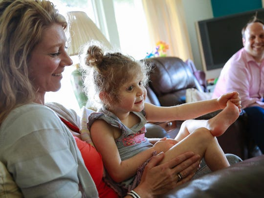 Bella Chinonis, 6, sits on the lap of her mom, Ida