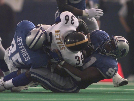 "Detroit Lions defenders Greg Jeffries and Robert Porcher tackle Pittsburgh Steelers running back Jerome Bettis in the second quarter of their Thanksgiving game on Thursday, Nov, 26, 1998 at the Pontiac Silverdome. The Lions beat the Steelers, 19-16, in overtime after referee Phil Luckett heard Bettis call ""heads"" during the overtime coin toss. Bettis, to this day, says he called ""tails."""