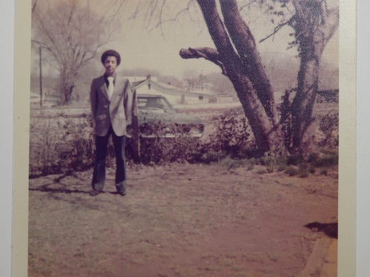 In 1971, a 17-year-old Dwayne Tucker stands near his first car, a 1969 blue Camaro, on the side of his childhood home in North Nashville.