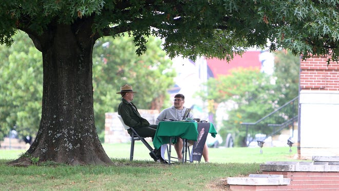 Park Ranger Cody Faber, left, and Southside High School intern Zachary Cozart set outside of the Fort Smith National Historic Site Visitor Center, Friday, Sept. 25, as they wait to lead visitor tours. The park ground and trails will remain open to provide healthy options for the public with Park Rangers on duty Monday through Saturday, 10 a.m. to 4:30 p.m. for guided tours and to assist visitors.