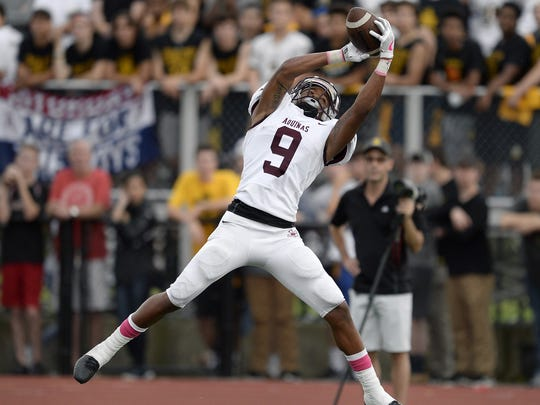 Aquinas' Marlek Connor Jr. reaches for an interception that he would return 100 yards for a touchdown during a regular season game at McQuaid Jesuit High School on Saturday, Oct. 7, 2017. Aquinas beat McQuaid 34-0.
