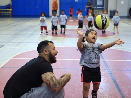 Coach Jimmy Valdez encourages Mia Ramirez, 3, as she misses her shot during the Summer 2017 Mini Dribbler Co-Ed Basketball League on Monday, July 31, 2017 at the Corpus Christi Gym. The league is for children ages 3 to 5 and introduces them to the sport of basketball and teamwork. Despite their skill level, every child gets an opportunity to get their hands on the ball and has positive encouragement.
