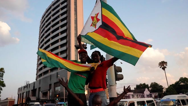 Civilians and soldiers celebrate after the resignation of Zimbabwe's president Robert Mugabe on Nov. 21, 2017 in Harare.