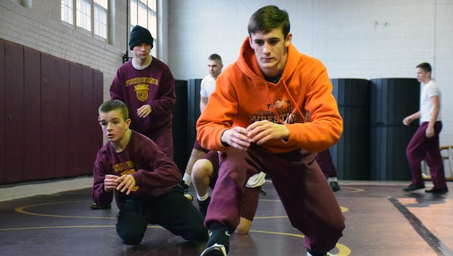 Matthew Farrar, a senior cadet at Fishburne Military School, leads the wrestling team through warmups before practice on Tuesday, Feb. 6, 2018, in Waynesboro, Va.,  Waters became the Caissons' coach in 2015, the same year Farrar transferred to Fishburne.