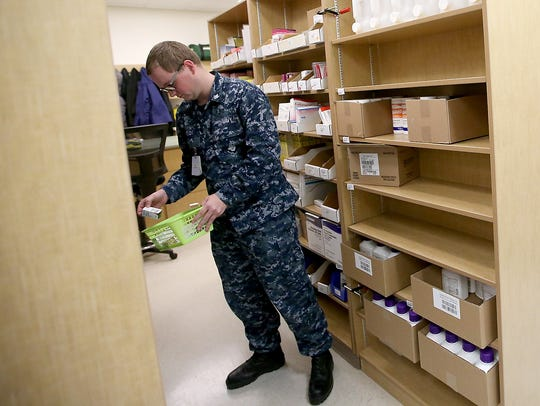 Hospital Corpsman Third Class Kyle Fields retrieves medications from the shelves as he fills prescriptions in the pharmacy at Naval Hospital Bremerton. In addition to renovations, the implementation of a new electronic medical records system has slowed wait times for patients waiting for prescriptions.
