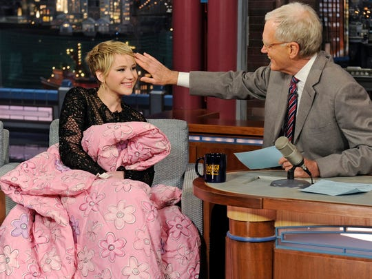 In this photo provided by CBS, host David Letterman brushes actress Jennifer Lawrence's bangs to the side on the set of the ?Late Show with David Letterman.