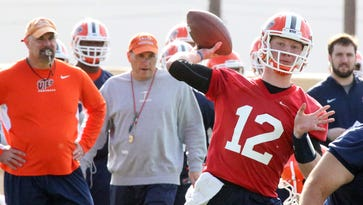 UTEP head football coach Sean Kugler, left, watches as quarterback Ryan Metz, 12, throws during the team's first spring practice Monday at Glory Field.