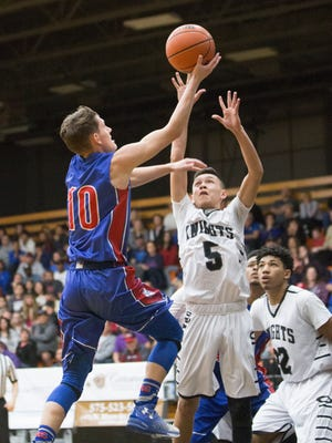 Las Cruces High's Cayden Sherwood (10) takes the ball to the basket as Oñate's Ricky Lujan (5) attempts to block his shot during the District 3-6A tournament championship game Saturday at Oñate High School. The Knights are the No. 1 seed for the Class 6A state tournament while the Bulldawgs are the No. 2 seed.