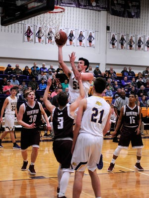 Wylie forward Kyle Roberts (55) goes over Brownwood's Xavier Porter (3) in the Bulldogs' 81-37 win on Friday, Feb. 9, 2018 at Bulldog Gym.
