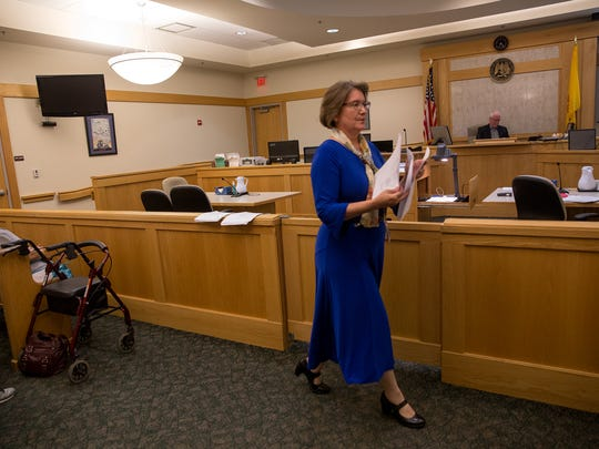 San Juan County 11th District Court deputy court executive officer Jodie L. Schwebel hands out papers Tuesday to residents during a name-change seminar.
