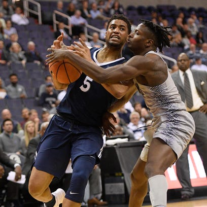 Georgetown guard Jonathan Mulmore, right, fights for