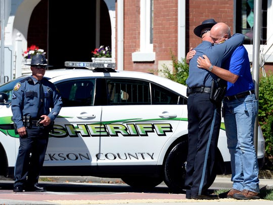 Dickson County Sheriff deputies comfort each other before the motorcade passes by carrying the casket of Dickson County Sheriff Deputy Daniel Baker on Monday, June 4, 2018, in Dickson, Tenn. Sgt. Baker, a Marine veteran, was shot in the line of duty last week.