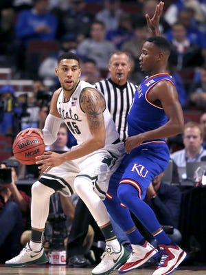 Michigan State guard Denzel Valentine, left, drives against Kansas forward Jamari Traylor Tuesday night in Chicago. Valentine finished with a career-high 29 points, to go along with 12 rebounds and 12 assists, his first triple-double.