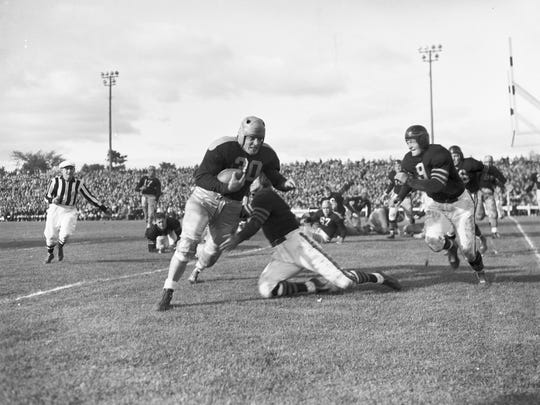 Green Bay Packers fullback Clarke Hinkle is hit by Chicago's Young Bussey as Bill Osmanski (9) closes in on him during the Bears' 25-17 victory at old City Stadium on Sept. 28, 1941.
