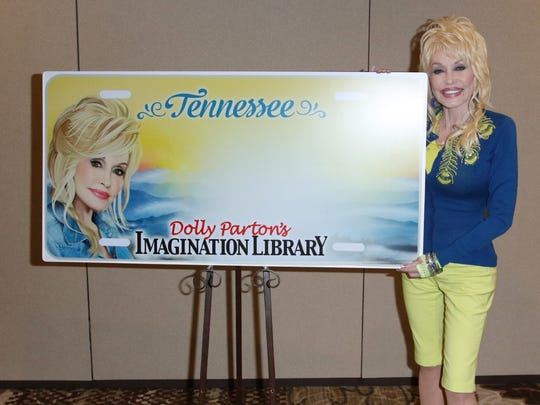 Dolly Parton poses with the new Tennessee license plate,