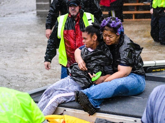 Evacuees are pulled from flooded homes in Northeast Houston on Monday.