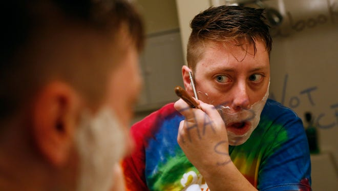 Jack Schuler shaves his face Friday, May 20, 2016, in the bathroom of his apartment before heading to work at Lincoln High School in Des Moines.