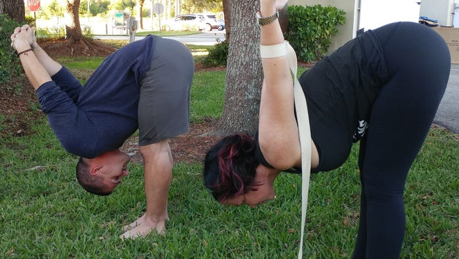 Jeremy Phillips and Heather Holland, of Ruby and Pearl's Yoga Studio, Fort Myers, demonstrate how to open the heart from the back.  Ruby and Pearl's Teacher Training begins in February.  Visit www.rubyandpearls.com for more information.