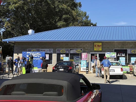 In this Oct. 24, 2018, file photo, media, at left, record people entering the KC Mart in Simpsonville, S.C., after it was announced the winning Mega Millions lottery ticket was purchased at the store.