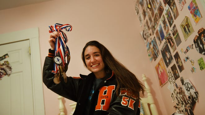 Giana DiLascio, a cross-country runner from Hasbrouck Heights who overcame obstacles after being diagnosed with hydrocephalus when she was 11, has become a champion runner. Here she is showing some of her medals in her room on Monday, Nov. 21, 2016.