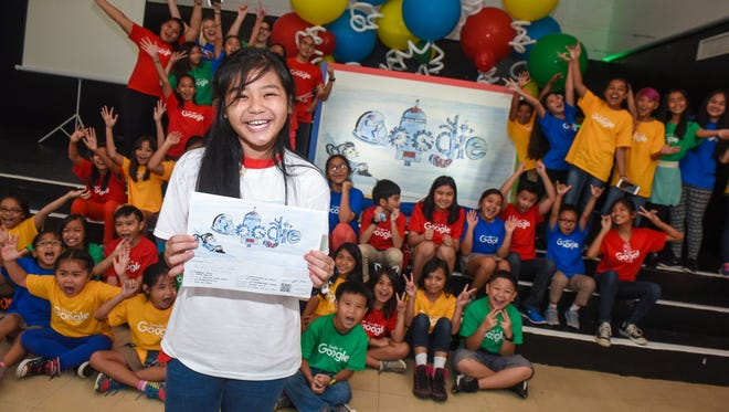 Fifth-grader Claire Danielle Fadul displays her original artwork entry as fellow students show their support after she was announced as Guam's winner in the ninth annual Doodle 4 Google competition at Upi Elementary School in Yigo on Thursday, Feb. 23, 2017. An online vote will be held for Fadul's entry and 52 other entries from the 50 states, Puerto Rico and the Virgin Islands, starting Friday, Feb. 24. The student with the entry that garners the most votes nationally, will receive a $30,000 college scholarship and his or her school will receive a $50,000 Google for Education grant towards the establishment and improvement of a computer lab or technology program, according to a Google website.