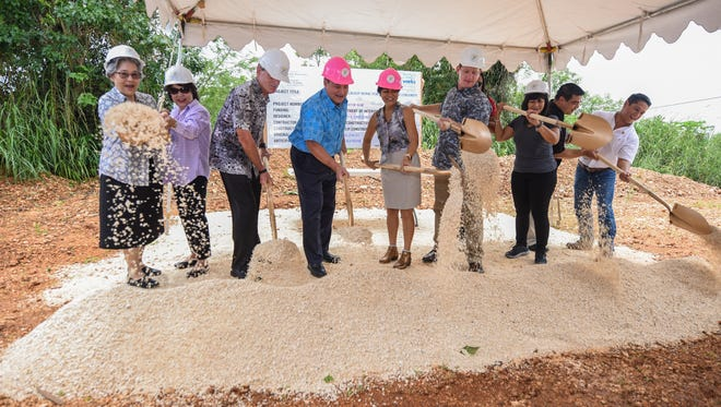 Gov. Eddie Calvo and first lady Christine Calvo, center, are joined by others in a ceremonial turning of the soil during the groundbreaking for a group home for foster care children in Barrigada Heights on Thursday, Oct. 12, 2017. The $1.14 million Department of Public Health and Social Services project is completely federally funded under the Department of Interior Compact Impact. The construction for the facility is slated to be completed by July 9, 2018, P&E Construction Project Engineer Alex Rabano said.