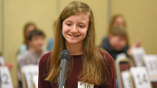 "Maggie Sheridan, an eighth-grader at Lexington Junior High School, smiles after spelling the final word correctly and winning the Richland County Spelling Bee on Thursday. Sheridan successfully spelled ""decrepitude"" to repeat as the county's champion."