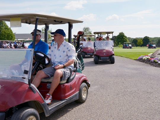 Golfers drive to their tee.