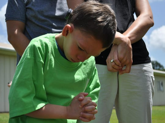 Hendrix Ebert prays after a balloon release in his honor at Elwood Baptist Church.