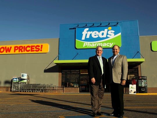 """In this Dec. 7, 2015 photo, Fred's president Michael Bloom and CEO Jerry Shore, left, pose for a photo outside of a store in Memphis, Tenn. Fred's, a small regional drugstore chain from Memphis, had a good week. It all started Tuesday, Dec. 20, 2016, when Fred's said it would pay $950 million to buy 865 stores that Rite Aid needs to sell in order to close a $9.4 billion buyout deal from Walgreens Boots Alliance Inc. The deal will more than double its current store count of 650, and Bloom called it a """"transformative event"""" for the company. (Nikki Boertman/The Commercial Appeal via AP)"""