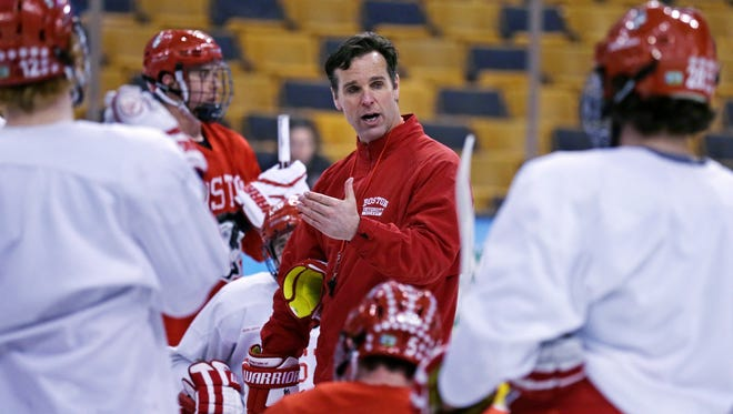 Boston University head coach David Quinn talks to his players during an NCAA hockey practice before the Frozen Four tournament in Boston, Wednesday, April 8, 2015.  (AP Photo/Charles Krupa)