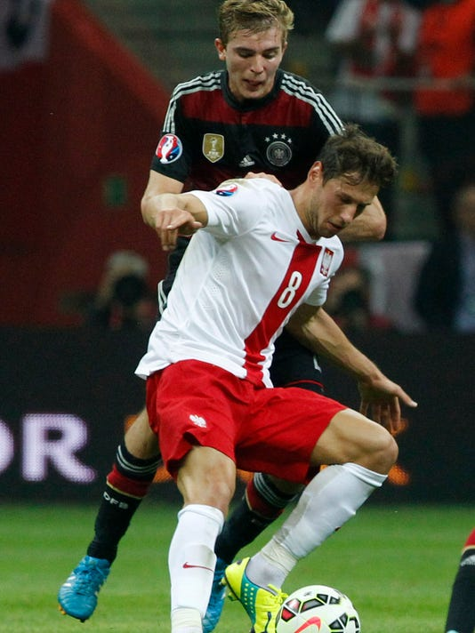 Poland's Grzegorz Krychowiak fends off Germany's Christoph Kramer during a Euro 2016 group D qualifying soccer match between Poland and Germany in Warsaw, Poland,Saturday, Oct. 11, 2014. (AP Photo/Czarek Sokolowski)
