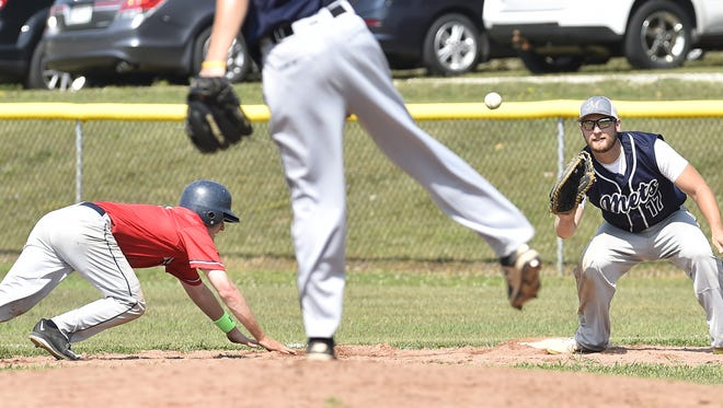 Egg Harbor baserunner Cory Fuller dives back to first base in a pickoff attempt as Maplewood's Kyle Ploor awaits the throw during Door County League baseball Sunday at Egg Harbor. Fuller was safe.