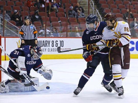 ASU's Ryan Belonger (16) tries to put a shot past Connecticut's