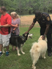 Deputy Duane Washington pets the two dogs he helped