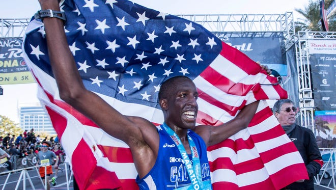 Roosevelt Cook, of Oak Hills, California, raises his hands in the air, draped with an American flag after winning the P.F. Chang's Rock 'n' Roll Arizona marathon. He clocked in with an unofficial time of 2:24:41 on Jan. 18, 2015, in Tempe, and he dedicated his win to his late mother who passed away earlier in 2014.