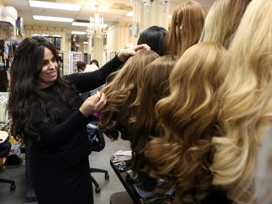 Owner Ayelet Berman organizes the wig display at L'Image salon in Monsey Feb. 27, 2018. Many Orthodox Jewish women cover their hair with wigs for the sake of modesty.