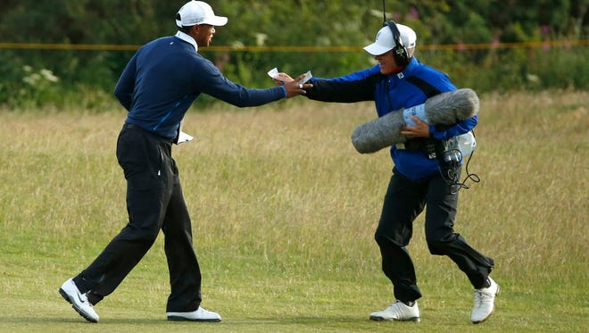 A sound man hands Tiger Woods his score card after it blew away in the wind during the second round of the British Open.