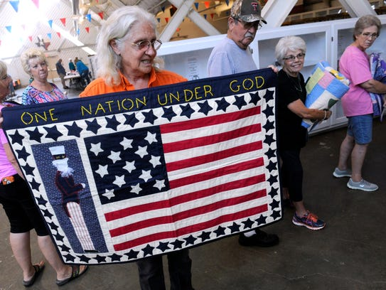 Susie Irvin of Merkel holds up a quilt made by her