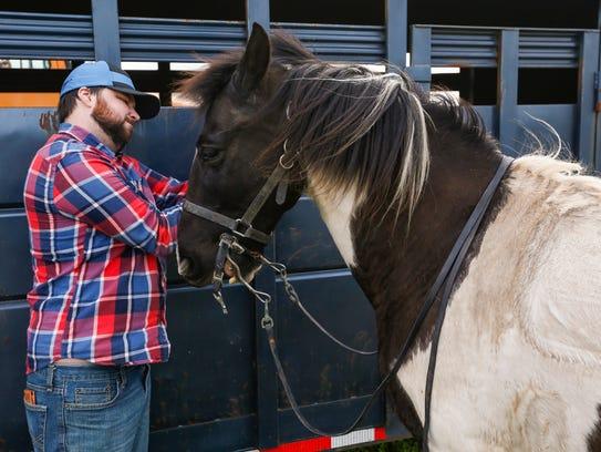 Landon Gardner takes off Duke's saddle after riding