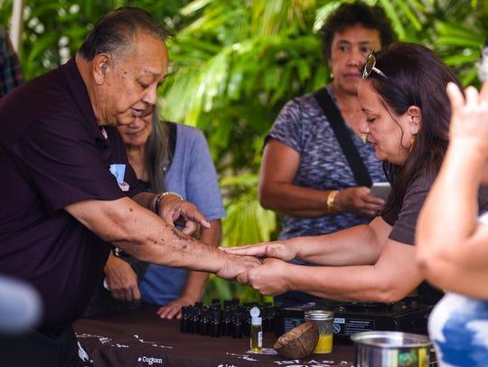 Participant Jose Cepeda, left, receives a rubbing of
