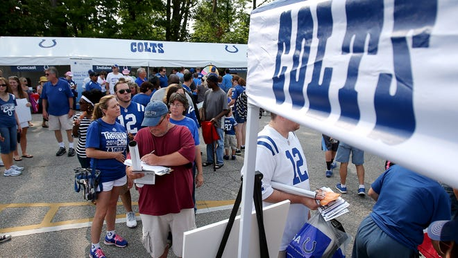 FILE -- Fans walk through Colts City before making their way to the Indianapolis Colts practice at training camp, on Thursday, July 31, 2014, in Anderson.