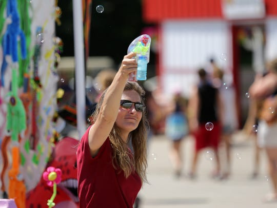 Melissa Robinson makes bubbles in front of her stand