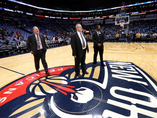 New Orleans Pelicans president Dennis Lauscha, left, walks on the court during a delay for the start of an NBA basketball game against the Indiana Pacers in New Orleans, Wednesday, Feb. 7, 2018. The game was under a delay due to moisture on the court falling from the rafters. (AP Photo/Gerald Herbert)