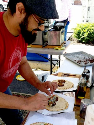 Amer from the Falafel Shack rolls up his signature falafel sandwiches.